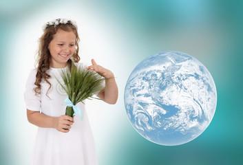 Dziewczynka w białym wianku z bukietem zboża.