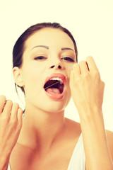 Beautiful young woman using dental floss