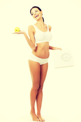Attractive fit woman with scale and apple