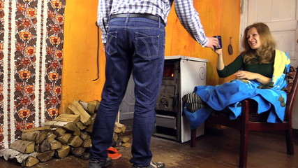 man bring girlfriend cup of tea and throw wood in old stove