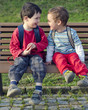Two children boys, friends or brothers sitting on a bench