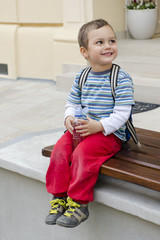 Child on bench with bottle of water