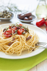 italian spaghetti pasta with cherry tomatoes, olives, capers and
