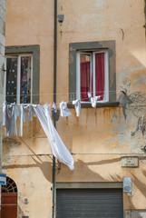 Finestra e bucato di panni lavati stesi, vestiti appesi