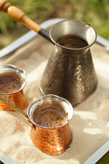 coffee preparation in copper pot with hot golden sand outdoor