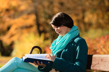 Girl relaxing in autumnal park reading book. Fall.