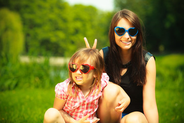 Summer. Mother and girl kid in sunglasses having fun