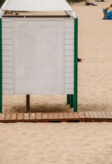 Summer resort. White dressing cabin on a sandy beach.