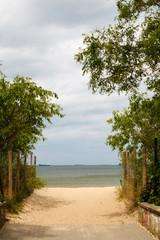Summer vacation. Entrance to a sandy beach. Seascape.
