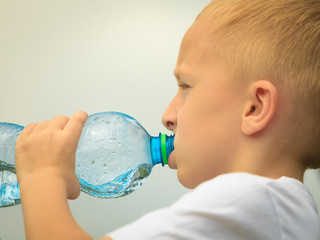 Child drinking pure water from plastic bottle
