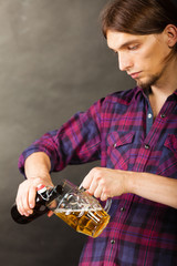 young man pouring beer from bottle into mug