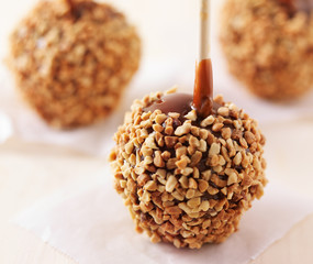 three caramel apples with nuts