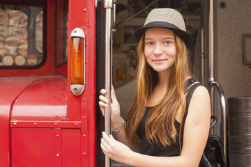 Pretty young hipster girl on a background of vintage red bus.