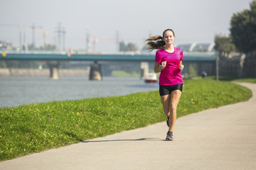 Young cute jogger girl runs on track along river in the city.