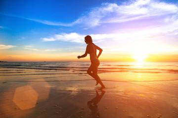 Young runner woman, jogging along the sea beach.