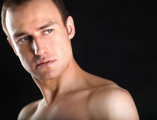Portrait of a naked muscular man, isolated on black