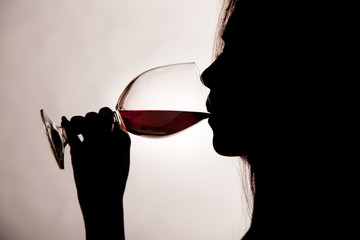 Silhouette shot of a female drinking red wine.