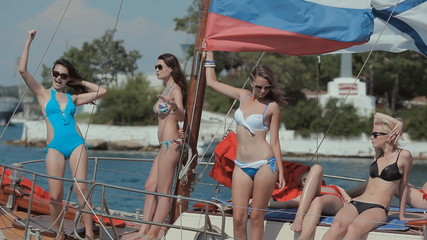 Amazing girl dancing on a yacht with Russian flag