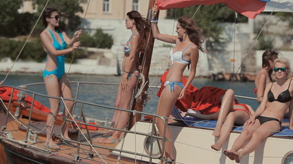 Beautiful slender girls having fun on a yacht that sails on the
