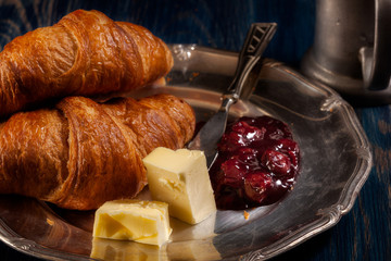 Croissants with butter and a glass of milk
