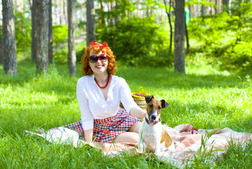 Pin-up girl playing with her dog on lawn