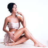 Fototapety Sensual young woman with beautiful body in the beige silk