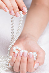 Beautiful woman's nails with french manicure  and pearls