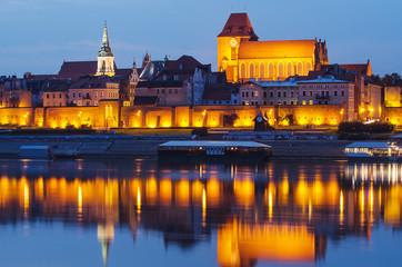 Torun (Poland) at night. The cathedral. View from Vistula river