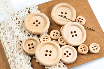 Wooden buttons, a needle and white lace on brown carton