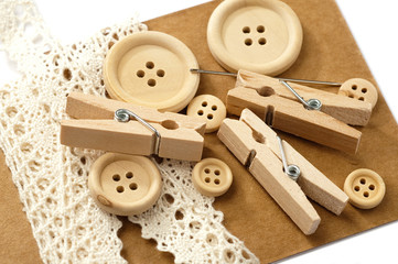 Wooden buttons, a needle, pegs and white lace on brown carton