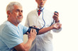Young doctor measuring blood pressure to a senior man. Isolated