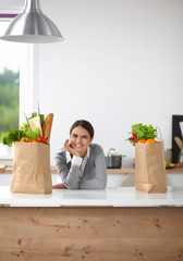 Portrait of a smiling woman cooking in her kitchen sitting