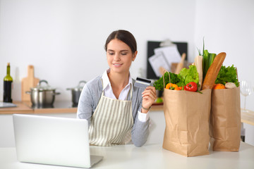Smiling woman online shopping using computer and credit card in