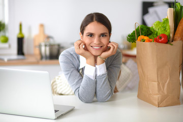 Beautiful young woman cooking looking at laptop screen with