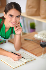 Happy beautiful woman standing in her kitchen writing on a