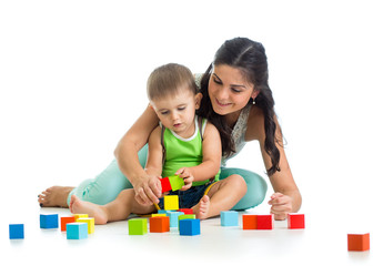 kid boy and his mother play together with construction set toy