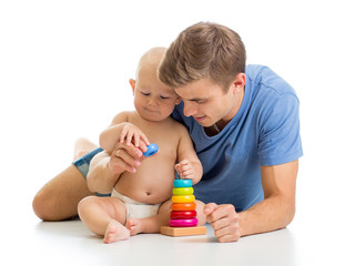 baby boy and father playing together with pyramid toy