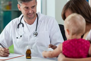 Pediatrician giving little girl a recipe