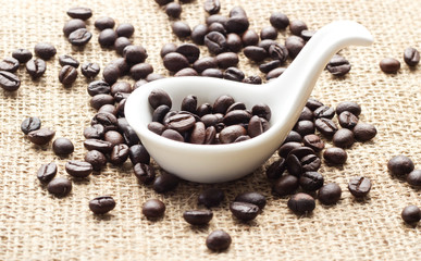 Coffee in spoon and sack background