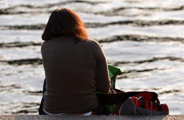 femme seule assise en bordure du fleuve