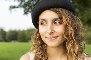 Attractive young woman in a hat smiling off camera