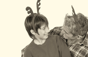 Kid joking with his father wearing Christmas props, Reindeer ant