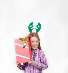 Happy baby girl wearing reindeer horns with a Christmas gift, is
