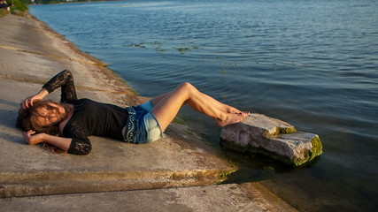 Sexy girl in short shorts lying near the water