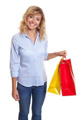 Frau mit blonden Locken und Einkaufstaschen