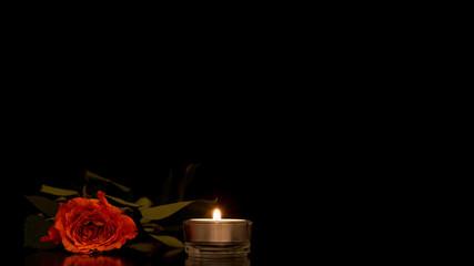 Single romantic orange rose with a burning candle