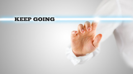 Hand Touching Keep Going Statement on Touch Screen