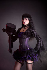 Magician assistant in purple and black gothic Halloween outfit