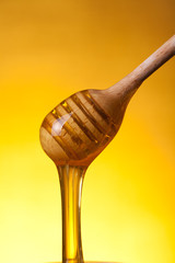 Close-up shot of wooden drizzler with flowing honey