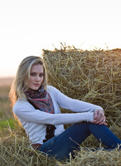 Girl sitting in a haystack